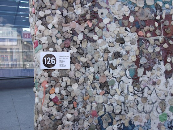 126 business card on berlin wall with a lot of gum